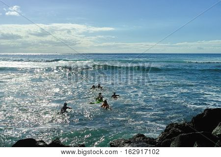 Surf school - several surfboarding students headed into an ocean swell on Tenerife Spain