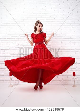 elegant woman in a long flittering red dress is standing in a white room with candles