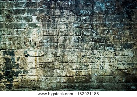 an old stone moist and weathered wall of brick stones