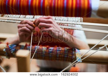 Hands engaged in production of handicraft textiles on the loom