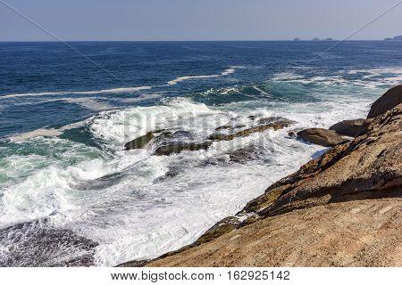 Waves crashing on the Arpoador stone in Rio de Janeiro