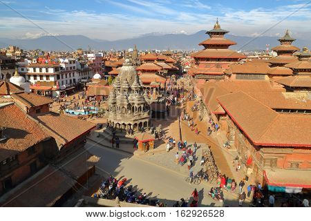 PATAN, NEPAL - DECEMBER 20, 2014: General view of the temples at Durbar Square with the Himalayan mountains in the background, Patan, Nepal