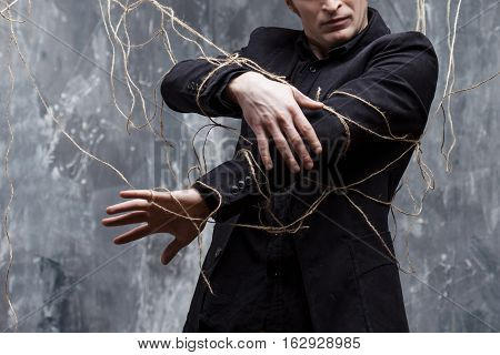 Young man tries to break the shackles. Concept of manipulation and slavery. Hands, close-up