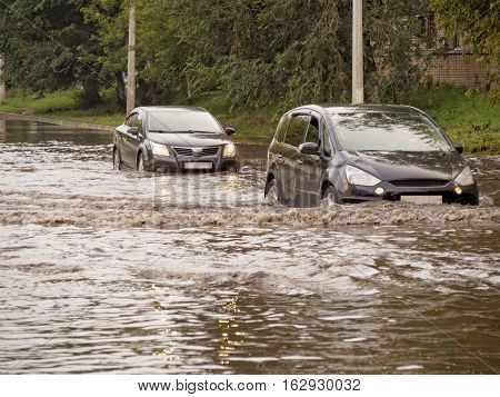 Cars on the street flooded with rain