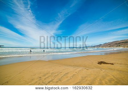 Some surfers in Pismo Beach in California