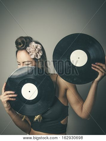 Laughing young fashionable woman with face behing two vinyl LP records studio background