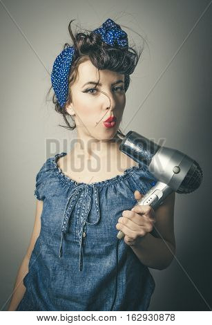 Half body portrait of housewife in vintage clothes pointing modern hair dryer at face