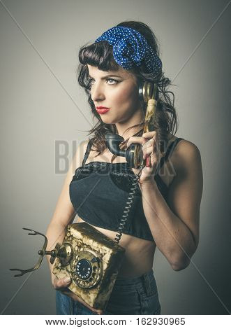 Half body portrait of thoughtful fashionable young woman in vintage clothes with retro telephone studio background
