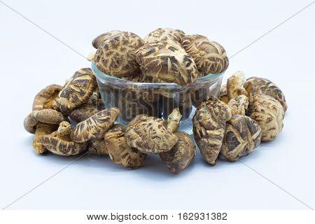 Dry mushroom on glass bowl, on white background