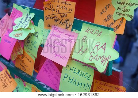 Donetsk Ukraine - 23 December 2016: Stickers on a symbolic tree on Lenin Square with children's wishes for peace