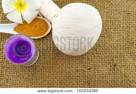 Spa herbal compressing ball white frangipani flowers (Plumeria spp Apocynaceae Pagoda tree Temple tree) turmeric powder in wooden spoon and candle on brown sack fabric background