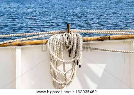 Coiled rope lines stored on belaying pin on a sailing vessel