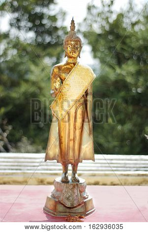 Small golden statue of a Buddha on the sanny day in Thailand