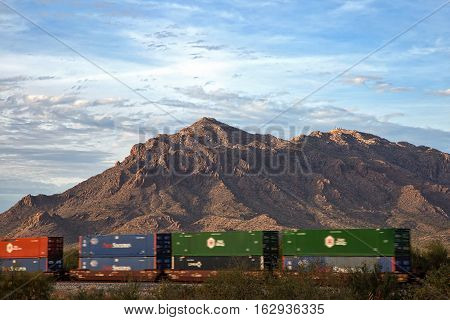 Railroad Freight cars in motion against the setting sun on the Picacho Mountains and Newman Peak