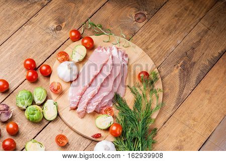 Slices of raw pork meat and vegetables