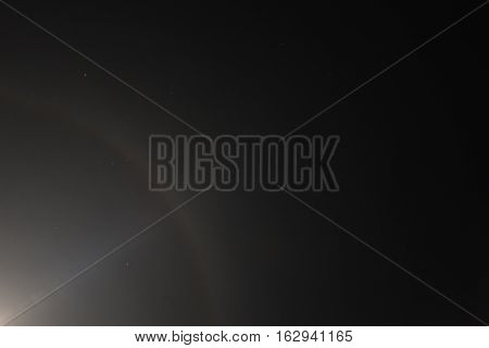 Dark night sky background with bright moon in the left-bottom corner