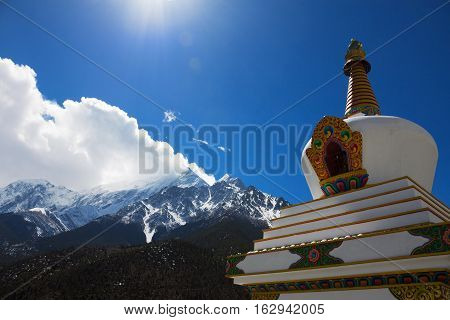 Buddhist Stupa near Jomsom with high rocky mountains on the background, Annapurna Circuit Trek, Himalayas, Nepal.