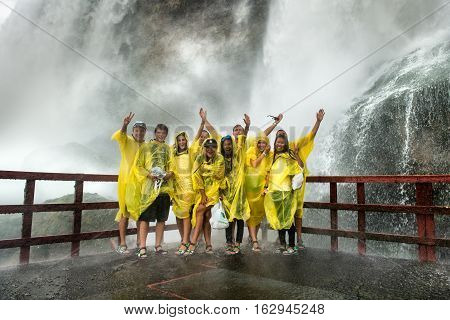 NIAGARA FALLS NY - JULY 13: Happy Visitors on Niagara Falls on July 13 2015 in Niagara Falls New York. Niagara Falls is the waterfalls with the highest flow rate in the world.