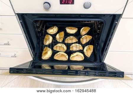 Fresh baked homemade cookies in oven. Tray of cookies coming out of the oven