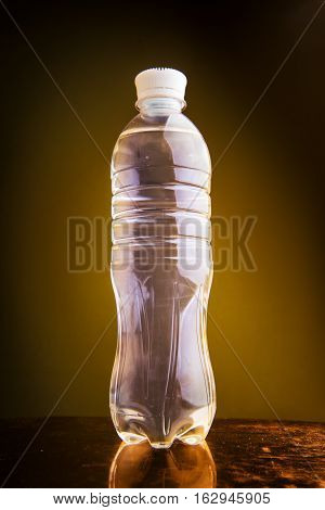 Water plastic bottle isolated on golden background