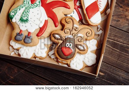 Craft box with Christmas homemade gingerbread cookies with reindeer on wooden table