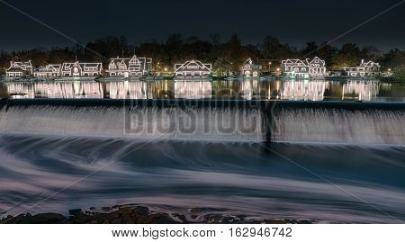 Illuminated houses along boathouse row reflect on the Schuylkill River.