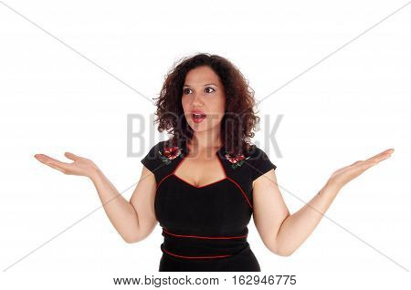 A beautiful young woman with curly brunette hair is frightened holding her hand to the side isolated for white background.