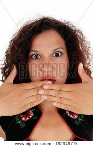 A beautiful young woman with curly brunette hair is frightened holding her hand over her mouth and her eye's wide open.