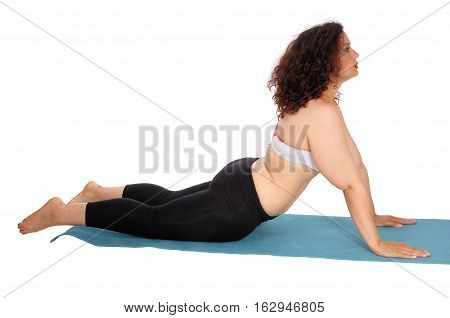 A young woman doing punch-ups on a blue mat with curly brunette hair wearing exercise outfit isolated for white background.