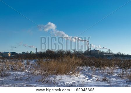 On the background of snow-covered vacant lot visible pipe of a thermal power plant with large pipes. Of the pipes coming out thick smoke polluting the atmosphere.
