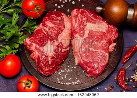 Raw meat, beef Ribeye and tomatoes, parsley and spices on a round cutting board. Juicy fragrant cut with a high degree of marbling