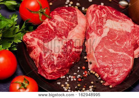 Raw juicy meat steak on a cutting board with tomatoes, spices. Ribeye is the most fleshy and marble of premium cuts.