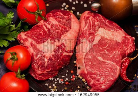 Marble beef for the perfect steak. Raw meat steak on dark wooden background ready to roasting with tomatoes, parsley and spices.