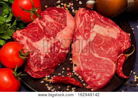 Still life from Raw beef steak with tomatoes, parsley and spices on black background from above
