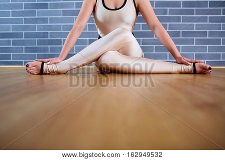 Girl in white clothes sitting  yoga gomukhasana position on  floor in the gym.