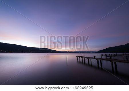 Glassy lake and purple sky at dawn