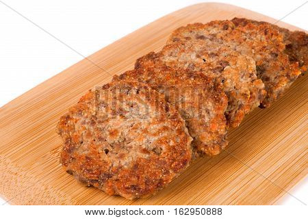 liver pancakes or cutlets on a cutting board isolated on white background.