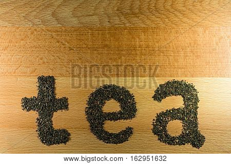 The word tea is laid out on a light-brown wooden Board small leaf black tea. Board is the background for the word tea.