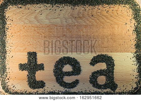 The word tea is laid out on a light-brown wooden Board small leaf black tea. Board is the background. The edges lined with a frame of tea.
