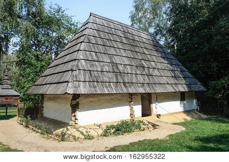 Lviv Ukraine - September 09 2016: Old Ukrainian peasant's house with wooden roof from Mukacheve district Zakarpattia region (1860). Museum of Folk Architecture in Lviv