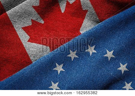 3D rendering of the flags of Canada and European Union on grunge woven fabric texture. Canada-European Union Comprehensive Economic and Trade Agreement (CETA) concept.
