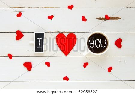 St Valentine's Day vintage overhead composition of I love you confession with hearts and coffe mug on wooden background