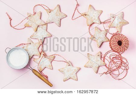 Christmas homemade gingerbread star shaped cookies with sugar powder in sieve and red decoration rope over light pink background, top view, copy space, horizontal composition