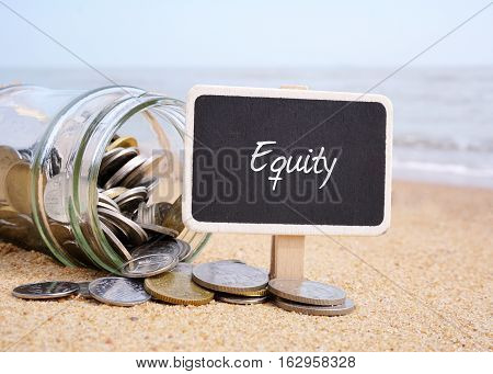 Wooden tag written with Equity. Coins and jar on blue ocean background.