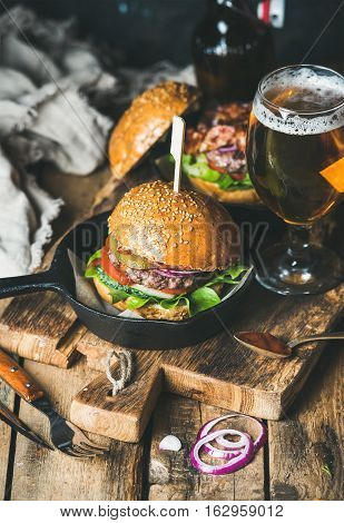 Homemade beef burgers with crispy bacon and vegetables in small pan and glass of wheat beer on rustic serving board over shabby wooden background, selective focus, vertical composition