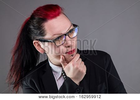 Thinking business punk woman in glasses on gray background