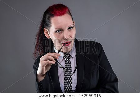 Boss punk woman with glasses on gray background