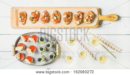 Brushetta sandwiches with tomatoes, gazpacho shots, desserts with berries and champagne in glasses, straws on corporate event, christmas, birthday, wedding celebration over white background, top view
