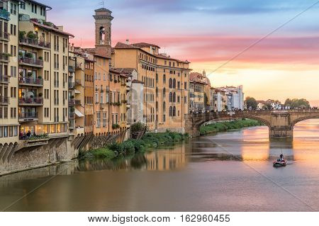 Sunset view of bridge and Arno river from Ponte Vecchio in Florence Italy