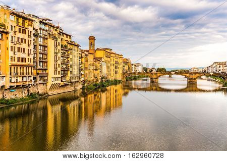 Apartments and bridge on the Arno river with reflections